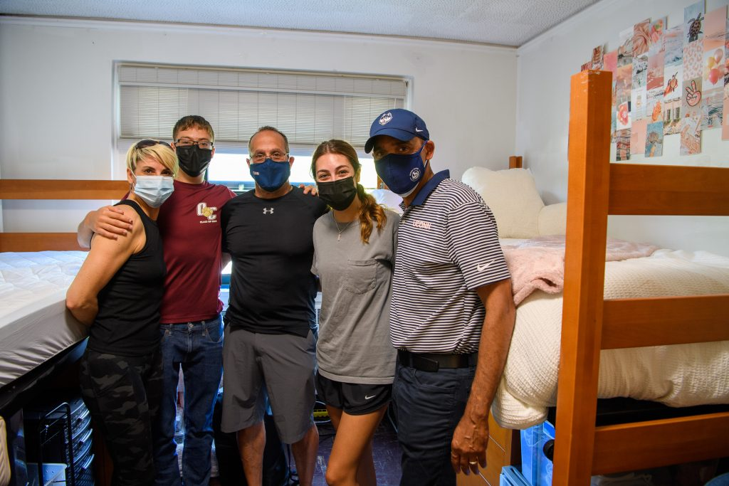 Andrew Agwunobi, interim president, right, visits with Nina Castillo '25 (CLAS) and members of her family at her room at the Towers Residence Halls on Aug. 27, 2021. (Peter Morenus/UConn Photo)
