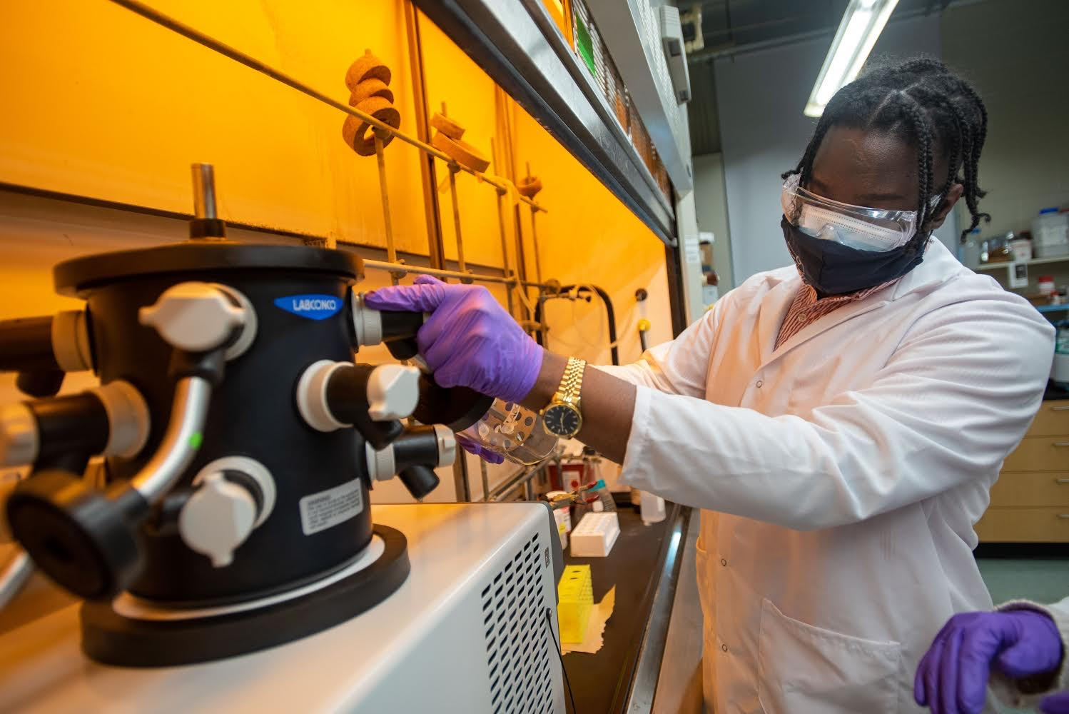 Nichali Bogues conducts an experiment wearing face masks and goggles in his lab.