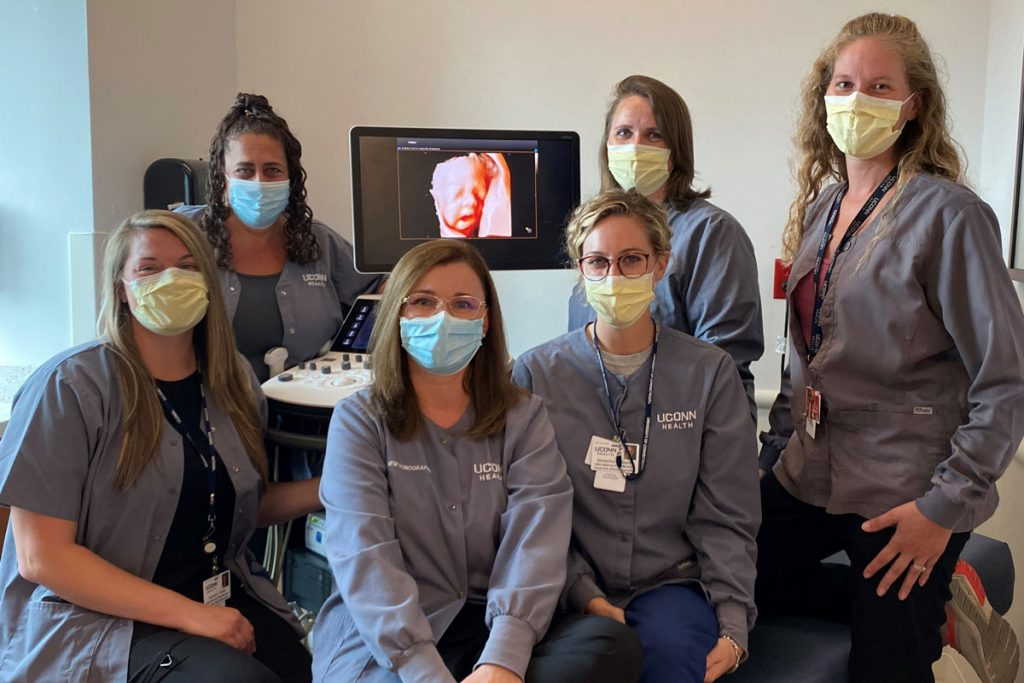 sonographer group portrait in front of ultrasound machine