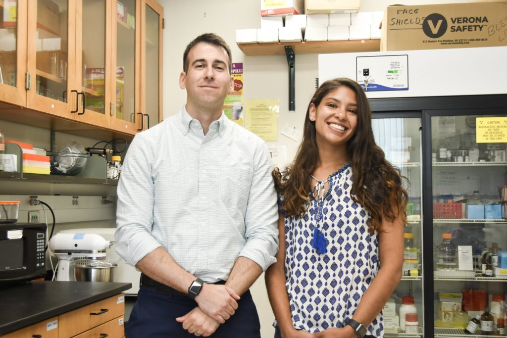 Man and woman smiling in a lab