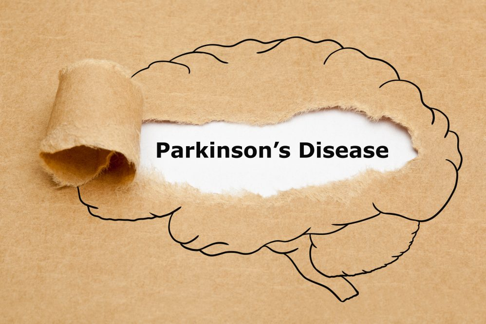 Concept with text Parkinsons Disease appearing behind torn brown paper with human brain drawing.