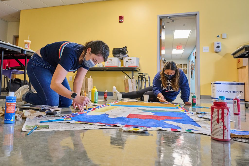 Brunna Louzada '22 (SFA), left, and Kate Gavilanes '22 (CLAS) paint a banner for the the homecoming parade at the Puerto Rican / Latin American Cultural Center on Oct. 1, 2021.