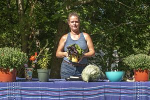 Lauren Haff standing at a table with her flowers and produce
