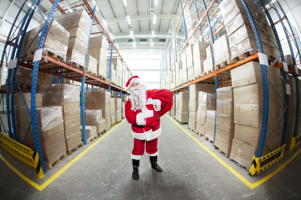 A person dressed as Santa Claus, standing in a warehouse. Pandemic-related supply chain issues have caused a shortage of popular consumer goods ahead of the 2021 holiday season.