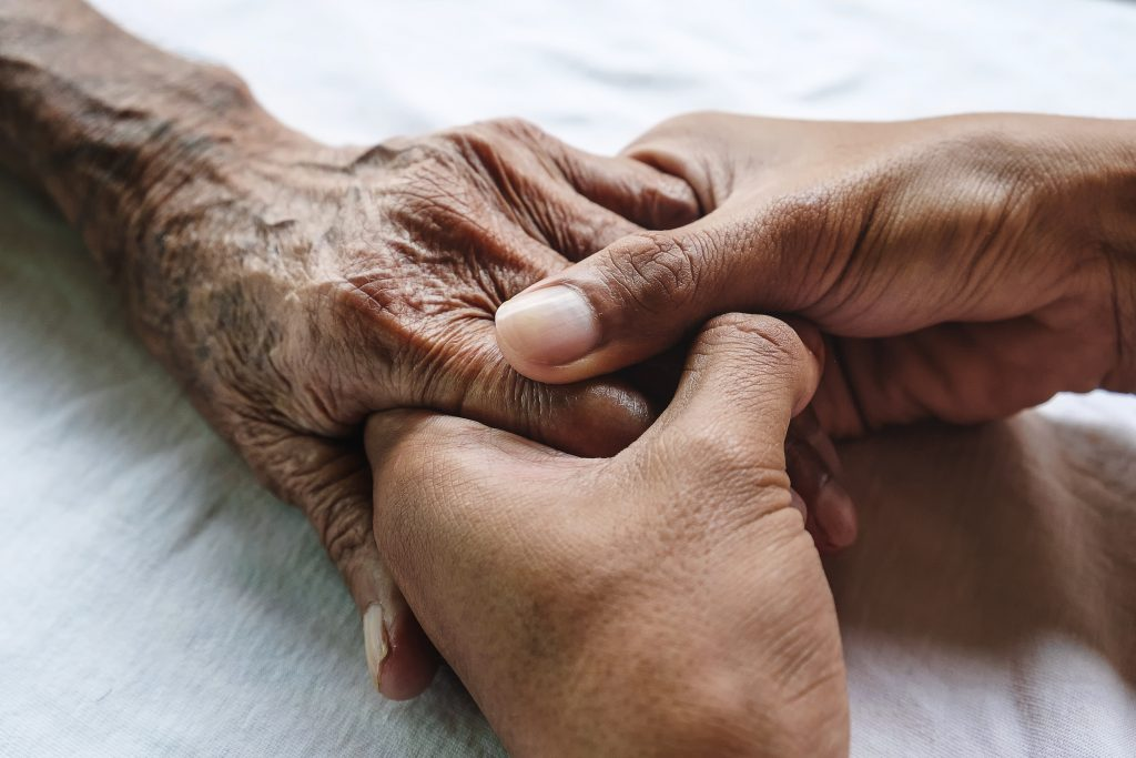 A younger man holds an older man's hands on a bed. UConn Health researchers have received a grant to investigate new methods of addressing health complications that come with aging.