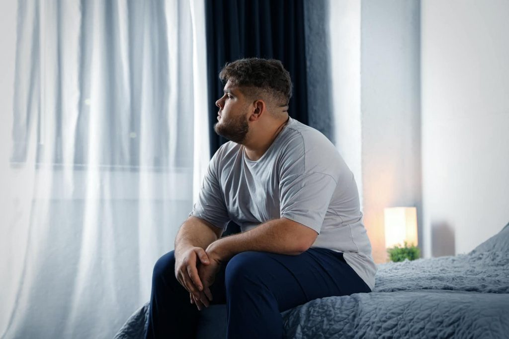 An overweight young man sits on a bed, gazing out the window with an air of melancholy. People with type 2 diabetes face stigma that can adversely affect their health.