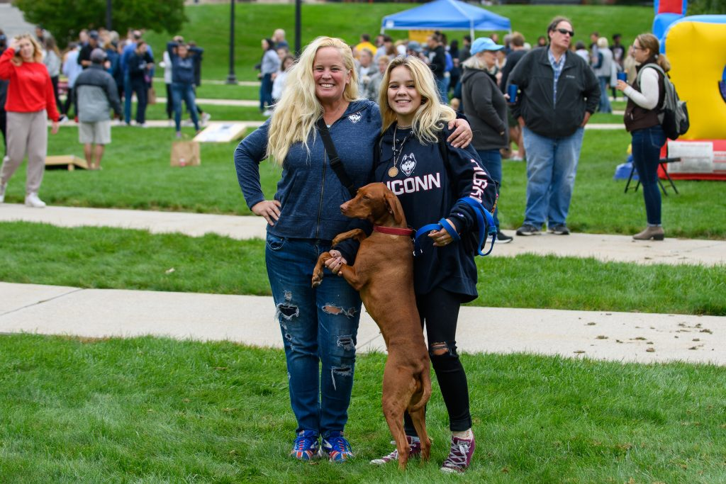 Prospective student Eve Kovac, her mom, Allison Kovac '97 and their dog at the Homecoming Carnival during Family Weekend on Oct. 10, 2021.