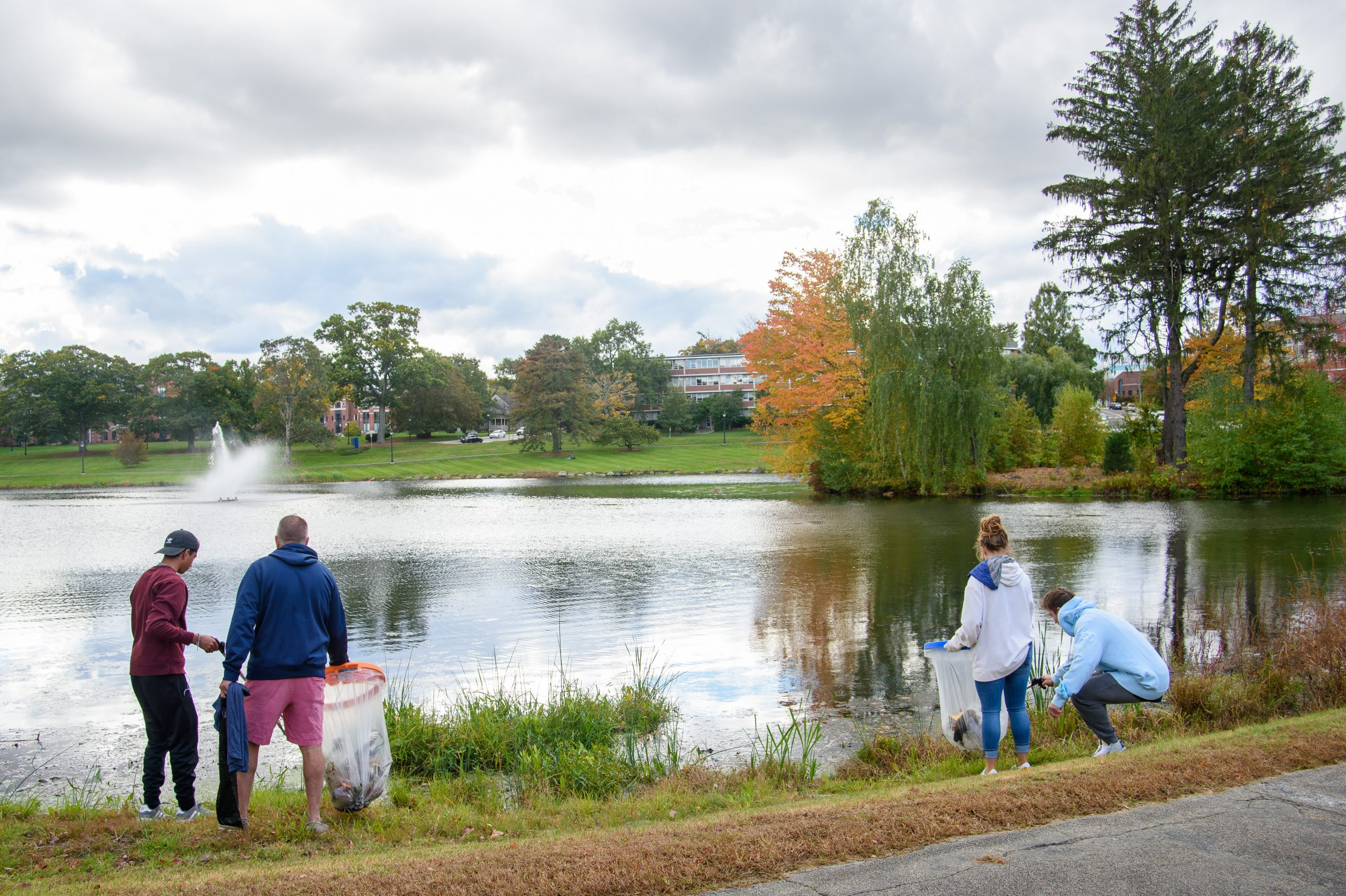 Jon Contaxis '25 (PHARM) left, his father Bill Contaxis '90 (ENG) of Milford, Rebecca Leelman '24 (ENG) and Nikita Karasik of Salem Mass. pick up trash around Mirror Lake on Oct. 17, 2021.